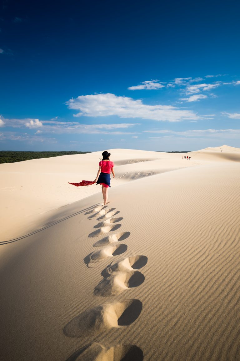 A girl walking on the sand dune of Du Pilat in southern France.