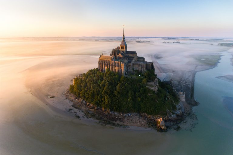 This image is taken in the Mont Saint-Michel during a pink sunrise with a little fog.