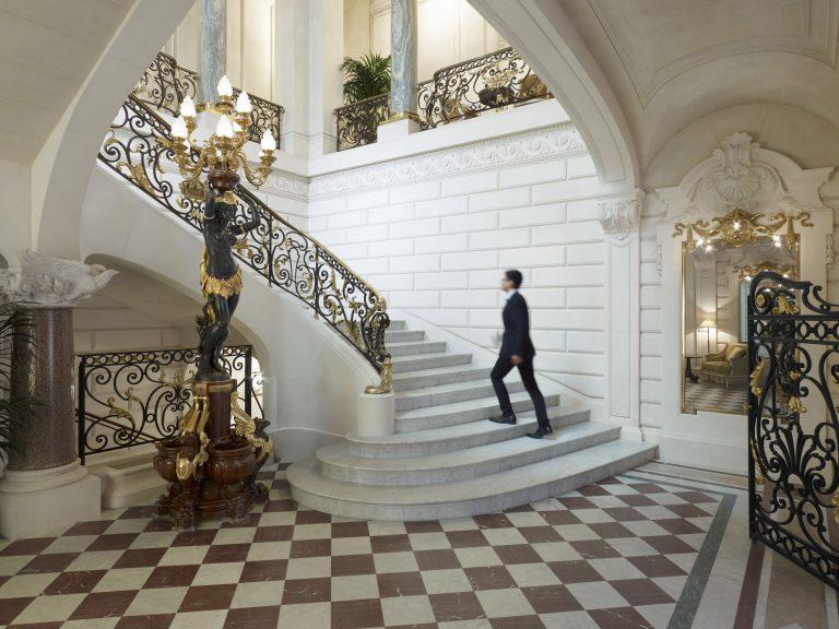Shangri-La Hotel, Paris_Historical Staircase with man at Shangri La Hotel Paris