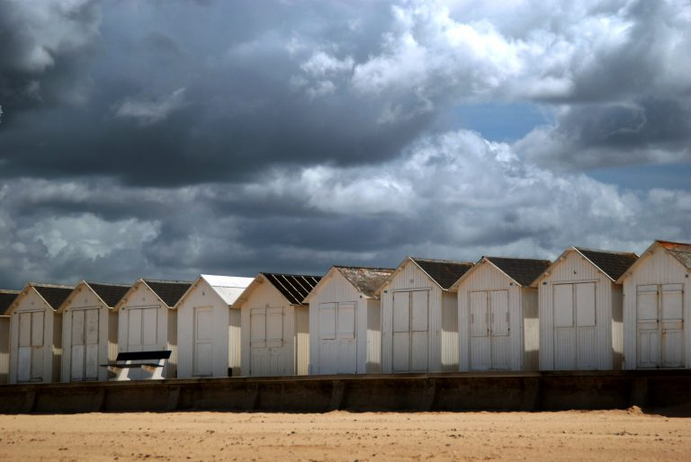 Small beach huts on the Normandy coast. Dramatic sky.